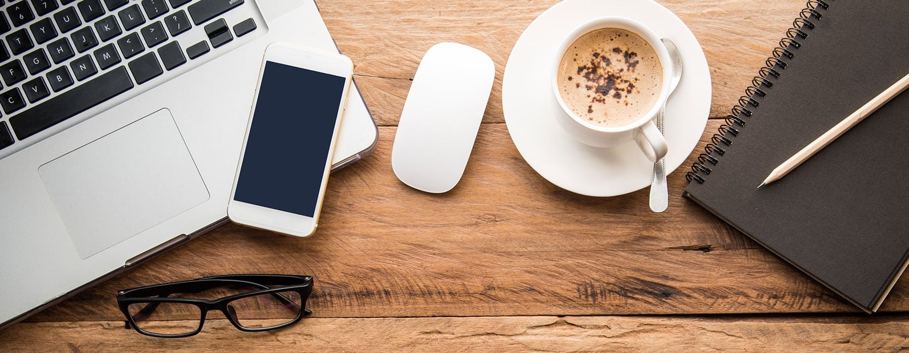 lifestyle image of communication devices, some reading glasses, and a coffee